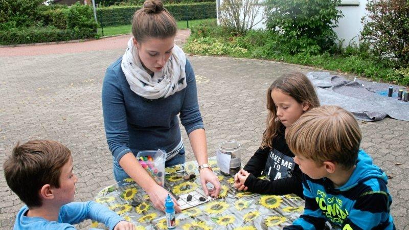 Betreuungsperson bastelt mit Kindern draußen