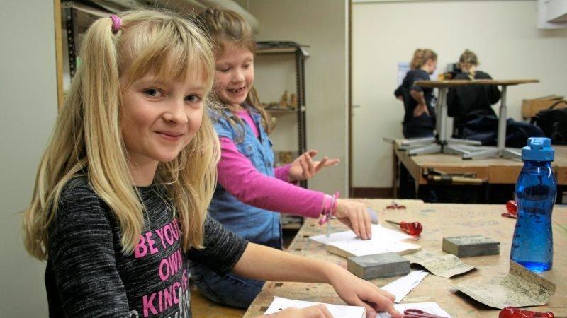 Mädchen werkt mit Holz und lächelt in die Kamera