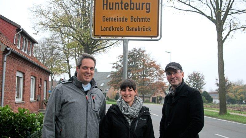 Drei Menschen stehen vor dem Ortseingangsschild von Huntebrug