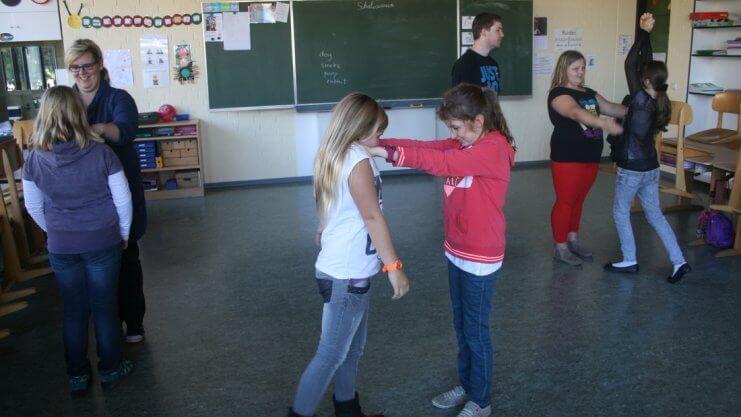 Mädchen lernen im Klassenraum sich selbst zu verteidigen