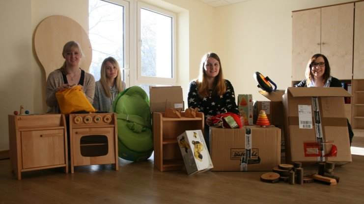Vier Frauen freuen sich über neue Spielsachen für den Kindergarten