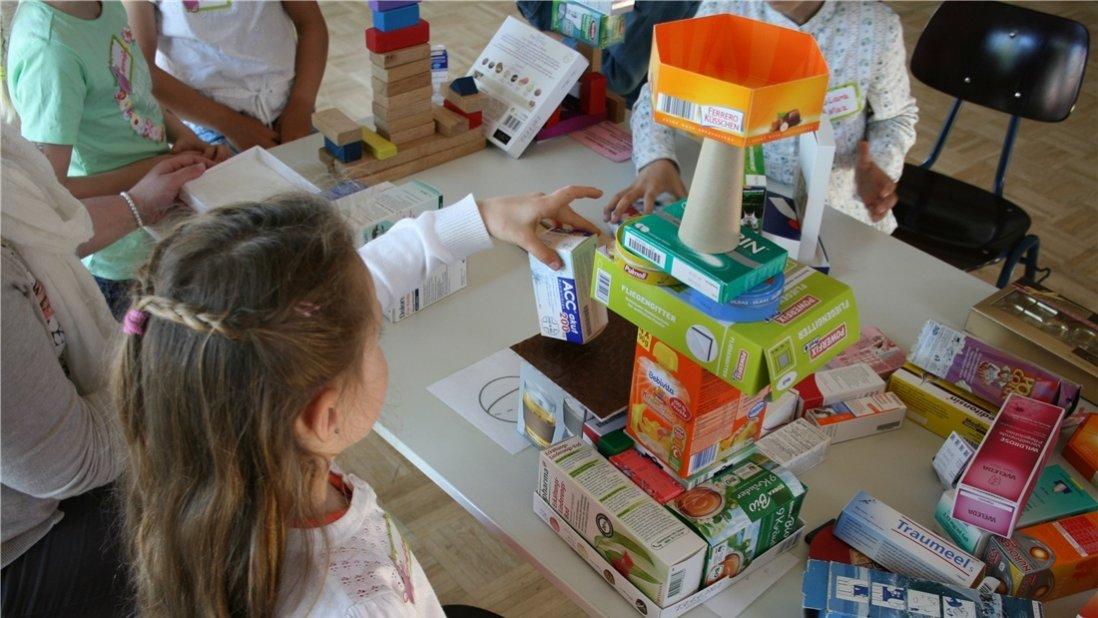 Kinder bauen einen Turm aus verschiedenen Verpackungen