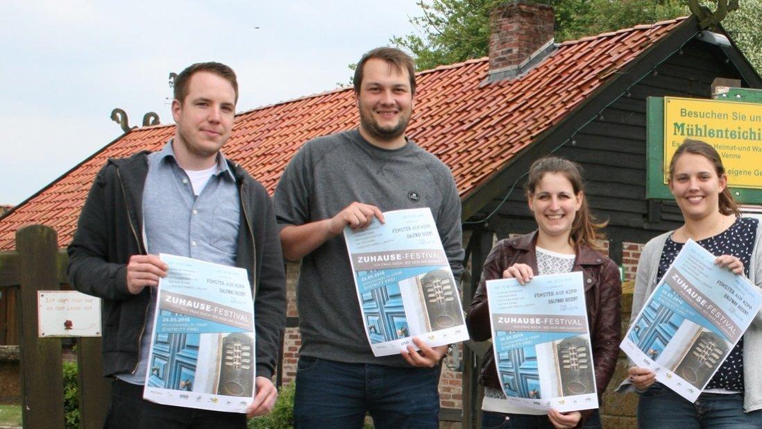 Vier junge Menschen präsentieren das Zuhause-Festival Plakat