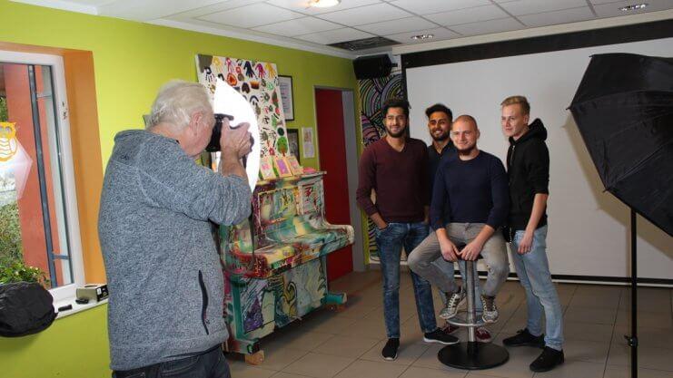 Ein Fotograf schießt ein Gruppenfoto von vier Männern