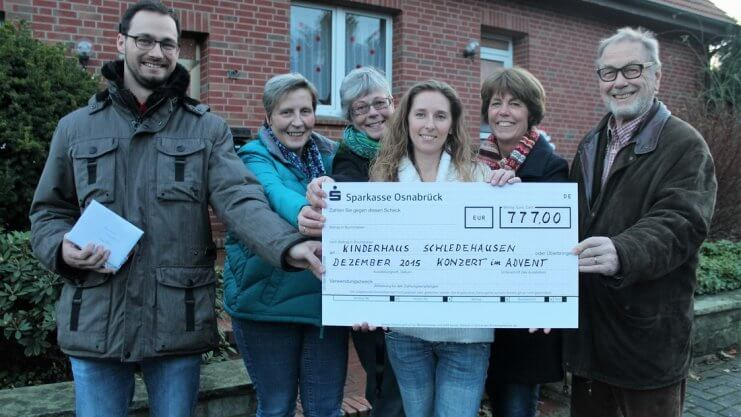Gruppenfoto mit einem großen Scheck für das Konzert im Advent