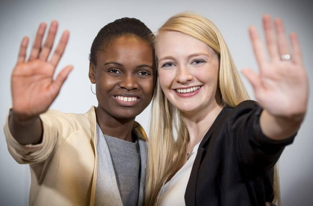 zwei Frauen lachen in die Kamera und zeigen ihre offene Hand in die Kamera