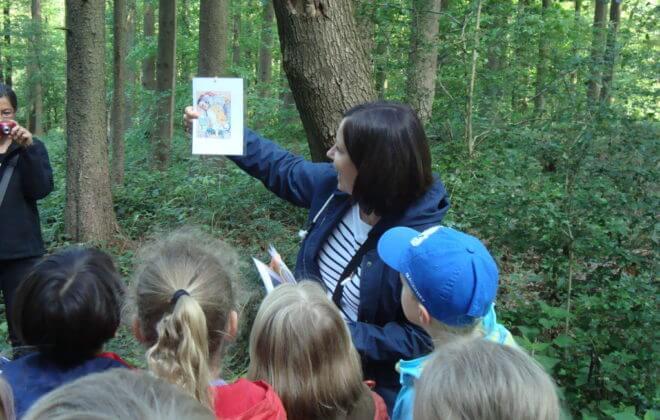 Betreuungsperson zeigt Kindern ein Bild im Wald