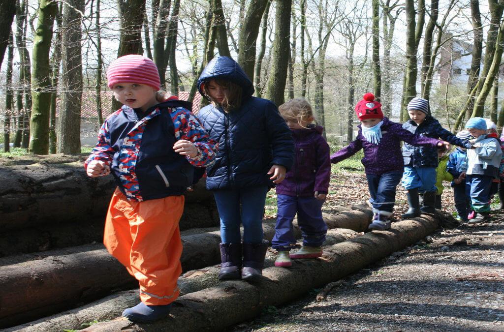 Kindergartenkinder balancieren über ein paar Baumstämme im Wald
