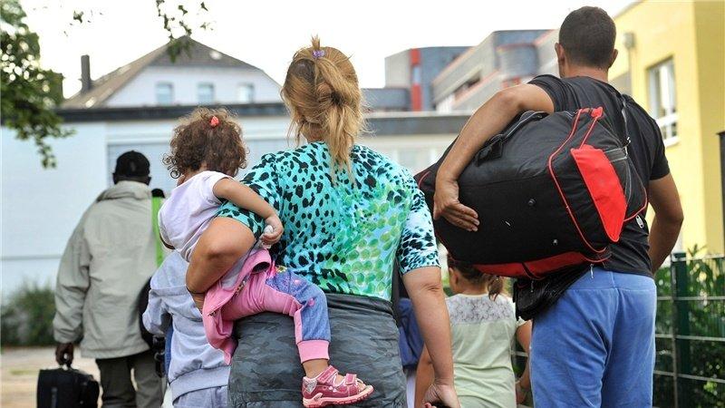 Flüchtlinge mit gepackten Taschen und einem Kind auf dem Arm