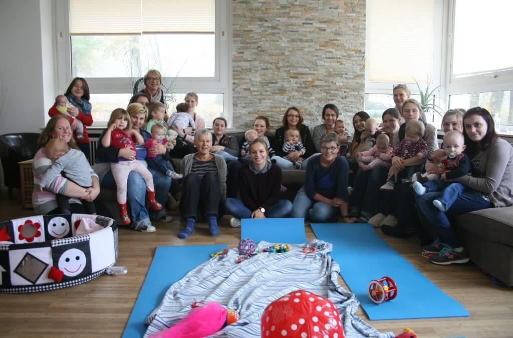 Mütter und Kinder mit Betreuungspersonen auf einem großen Sofa