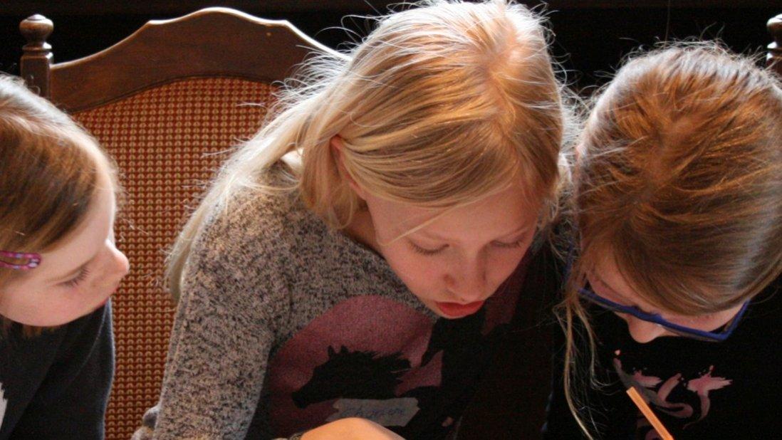 Drei Mädchen stecken die Köpfe zusammen