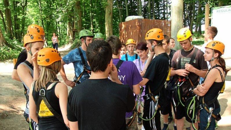 Jugendliche mit Helmen und Klettergeschirren warten im Kletterwald