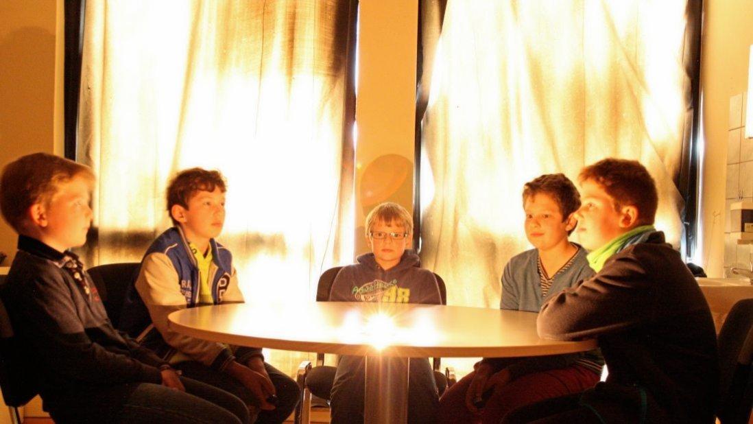 Fünf Jungen sitzen am Tisch und schauen sich an