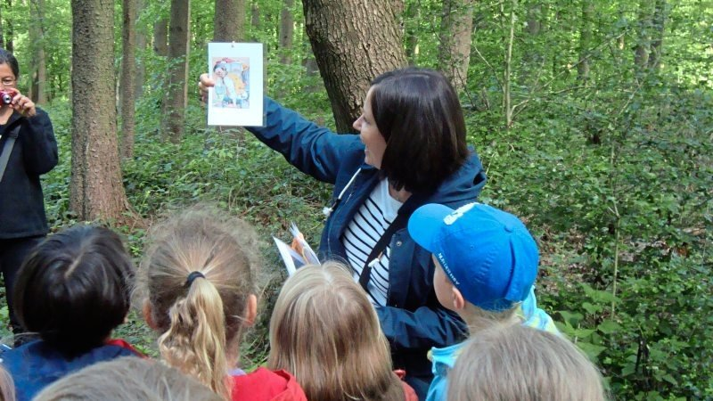 Betreuungsperson zeigt Vorschulkindern im Wald ein Bild