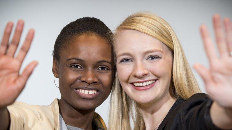 Zwei lächelnde Frauen winken in die Kamera