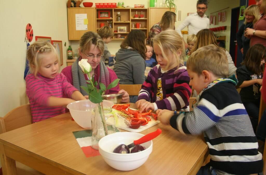 Kindergartenkinder sitzen gemeinsam am Tisch und schneiden Paprika
