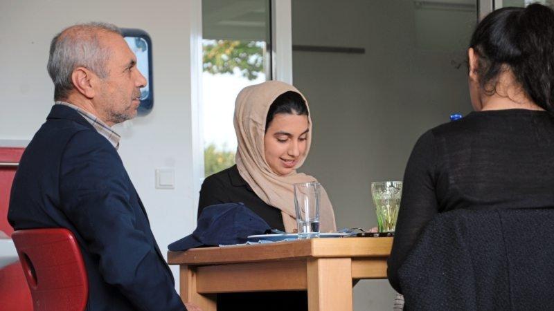 Ein junges Mädchen mit Kopftuch und ein älterer Mann sitzen am Tisch