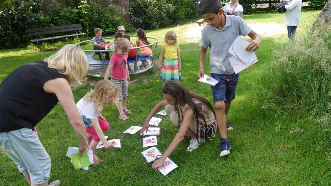 Kinder spielen draußen und legen Bilderkärtchen auf den Rasen