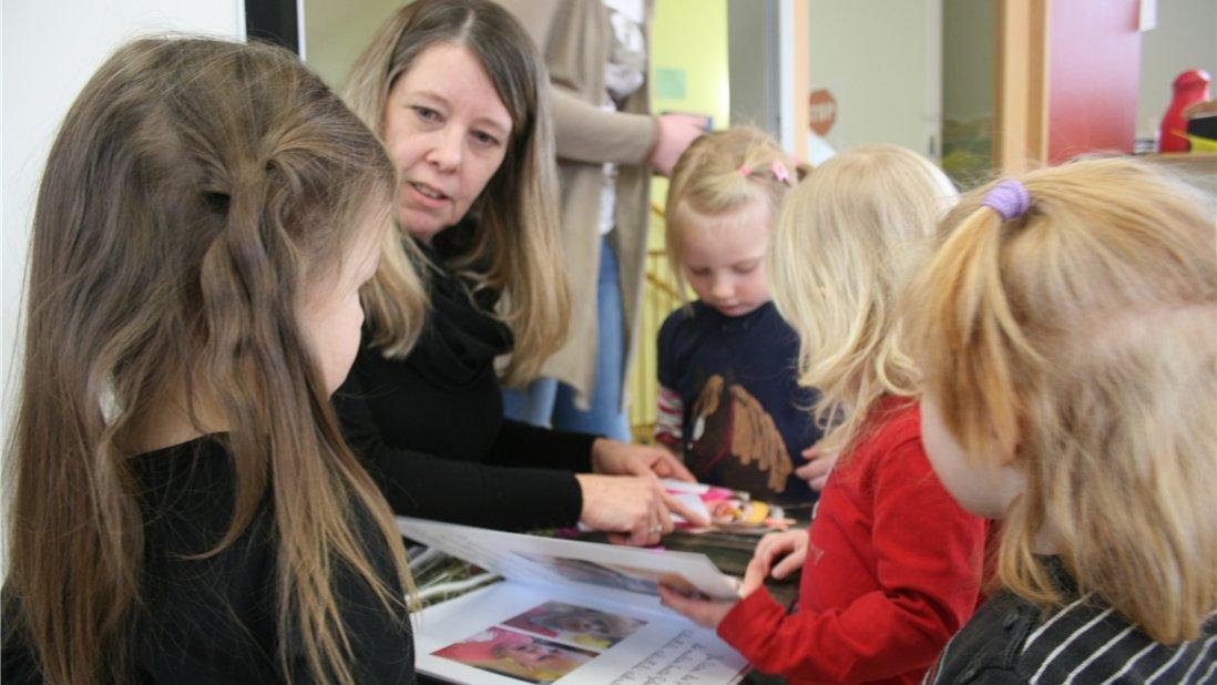Susanne Hermann schaut sich Bilder mit Kindergartenkindern an