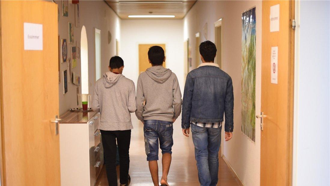 Drei Jungen gehen von der Kamera abgewandt den Flur entlang