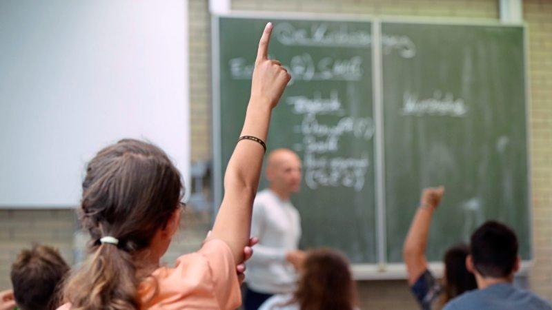 Detailaufnahme von einem Mädchen, welches sich im Unterricht meldet