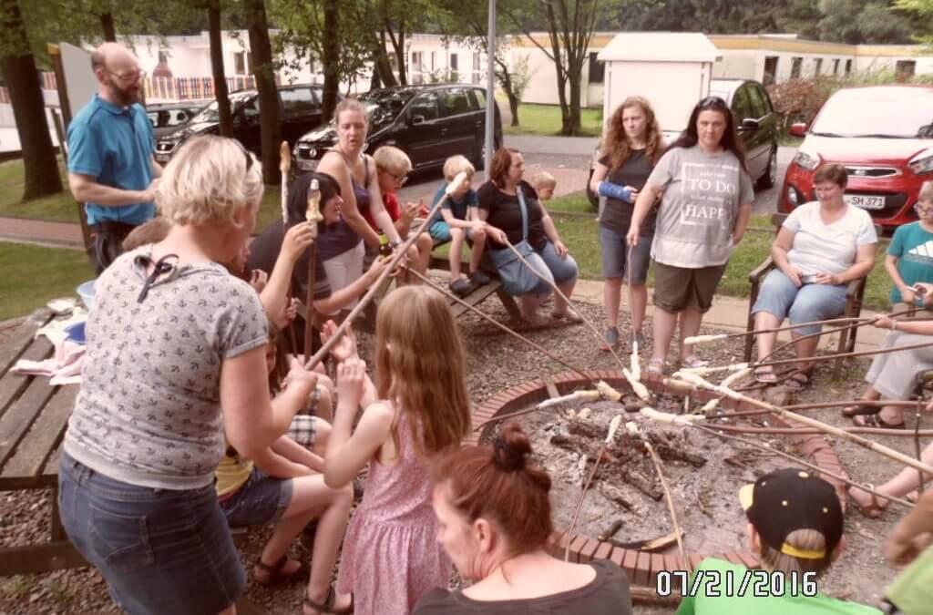 Gruppe von Kindern und Eltern grillen Stockbrot über einem Feuer