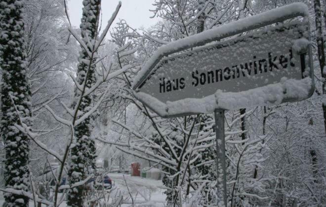 Schild zum Haus Sonnenwinkel im Winter voller Schnee