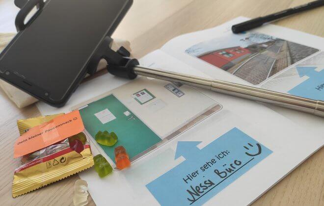 Selfiestick mit Handy, Gummibärchen und Unterlagen auf einem Tisch