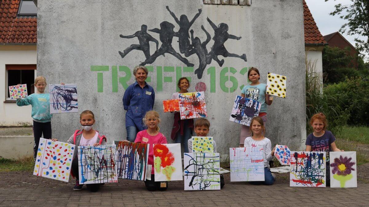 Gruppenfoto von Kindern mit ihren gemalten Bildern vor dem Treff 163