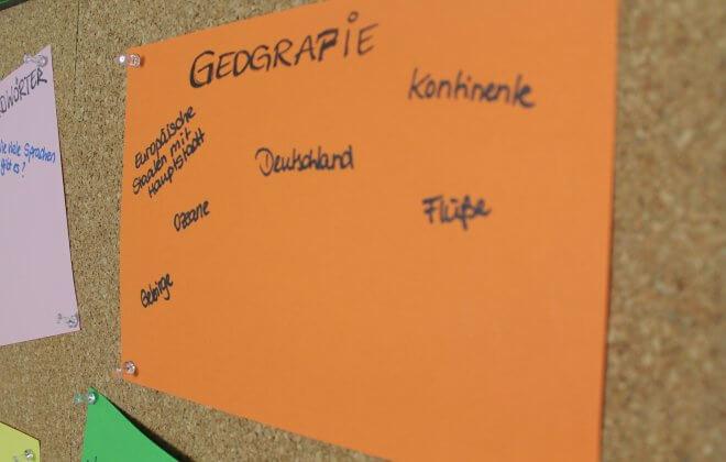 Pinnwand mit orangenem Plakat zum Thema Geografie