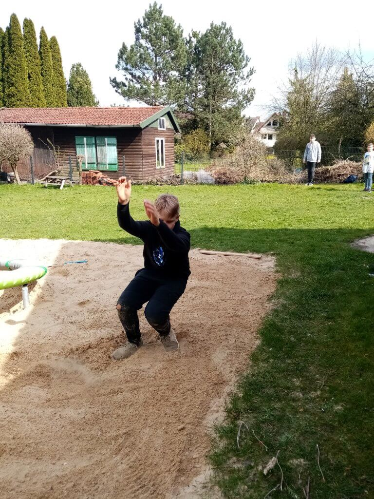 Junge macht einen Weitsprung in den Sand