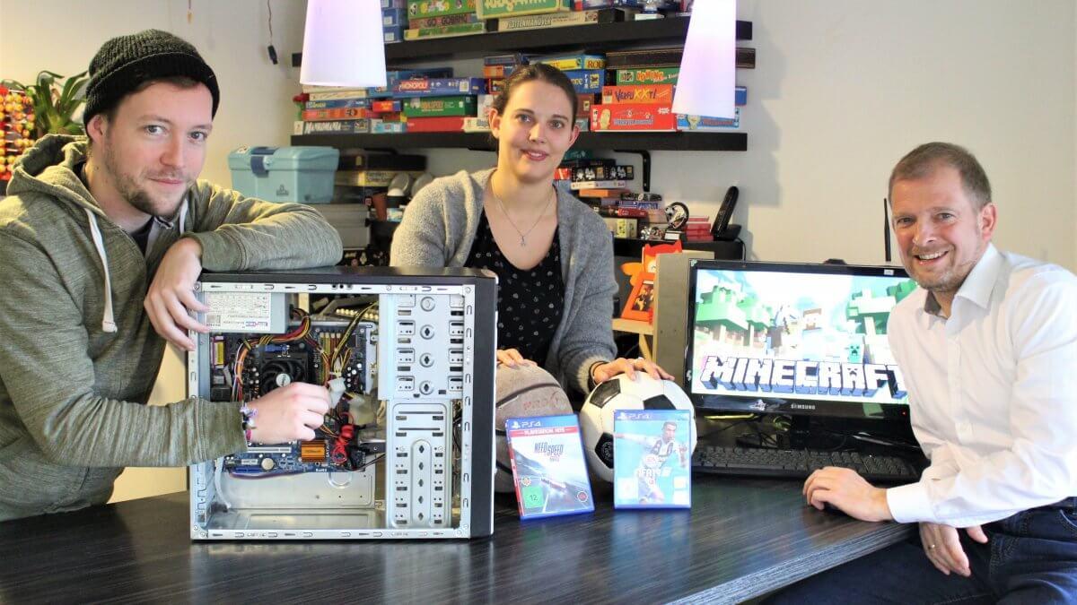 Gruppenfoto der Jugendhilfe - Sie präsentieren einen Rechner, Fußbälle, PlayStation Spiele und Minecraft