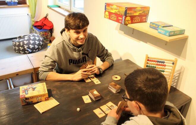 Praktikant spielt mit einem Jungen ein Kartenspiel